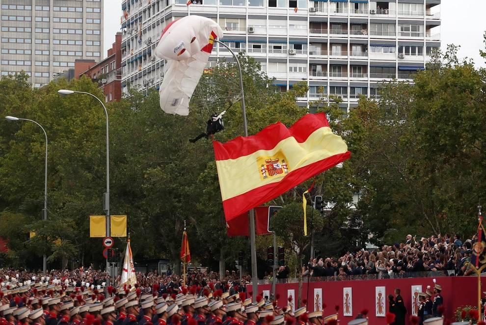 Un paracaidista se queda colgado de una farola durante el desfile